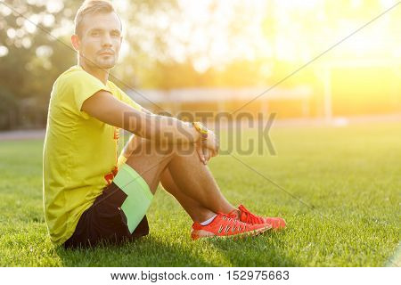 Young man athlete resting after workout. Image with lens flare effect