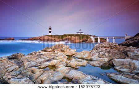 Idyllic view on seashore of Pancha island Spain at sunset of pink and purple colors