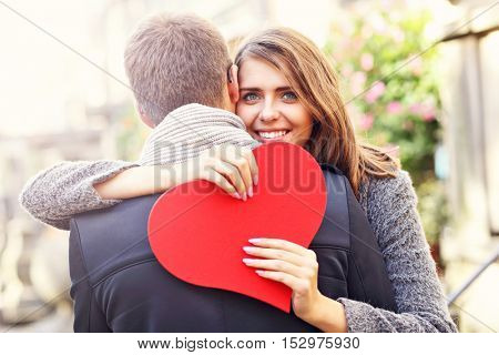 Picture showing happy couple hugging with flowers and heart in the city