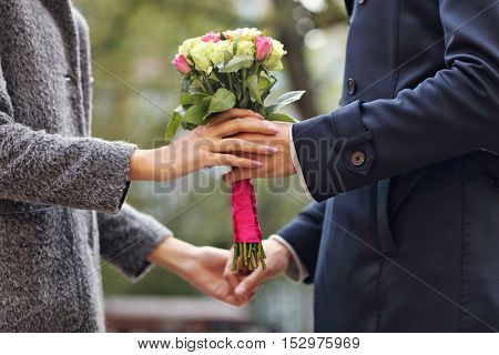 Midsection of young couple with flowers