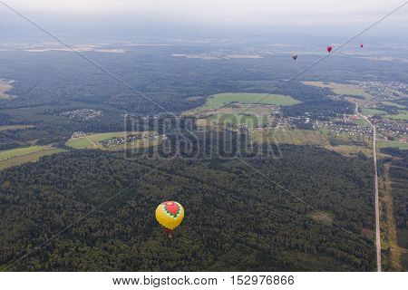 Aerial view of multicolored hot air balloon floating near trees