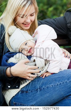 Happy mother with little daughter sitting on bench in autumn park