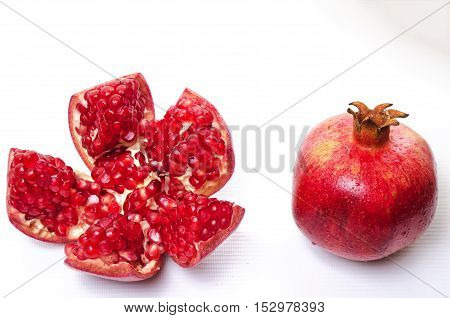 red and fresh pomegranate with water drops on a white background