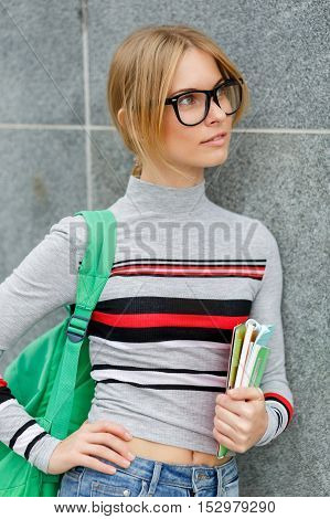 Thoughtful girl in glasses with backpack at gray wall