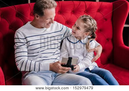 Mobile games. Smiling girl sitting on the couch with her grandfather and holding the game console while having fun at home