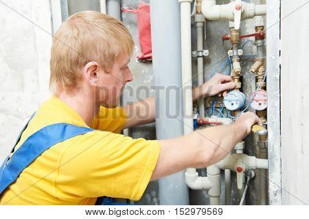 plumber man worker with spanner installing water meter