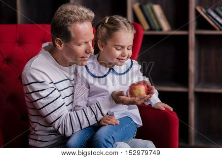 Family time. Joyful little girl sitting on the couch and looking at the apple with her grandfather while resting