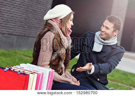 Picture of young man showing disapproval to woman with many shopping bags