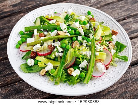 Fresh Green Asparagus salad witch Goat Cheese, peas, radish, zucchini, lettuce and Hazelnuts