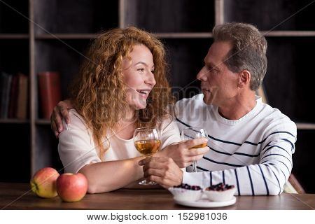 Time for two. Delighted aged woman and man drinking wine while resting at home