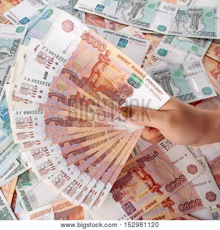 Female hand holding a large amount of russian money on the background even more roubles.