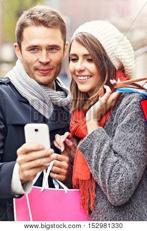 Young couple shopping in the city with smartphone