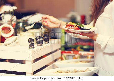 Midsection of woman at breakfast buffet in hotel