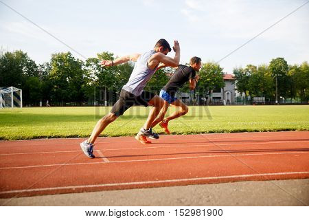 Two sports fast-running men on track outdoors on bright summer day