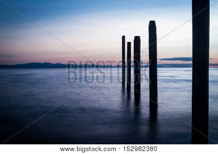 Night picture of Point Roberts pilings and silky water at night time