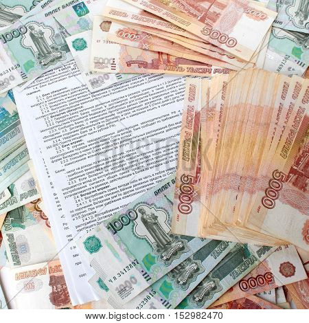 Bank deposit contract in Russian on the background a large number of rubles.
