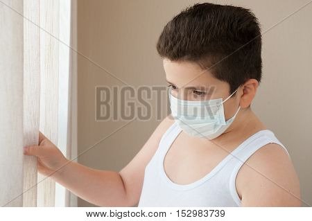 fat boy wearing a shirt and a surgical mask looking out the window in hospital