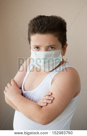 fat boy wearing shirt and surgical mask looking at the camera