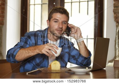 young attractive businessman or student on his 30s wearing casual clothes working or studying with laptop computer at coffee shop busy talking on mobile phone in modern business concept