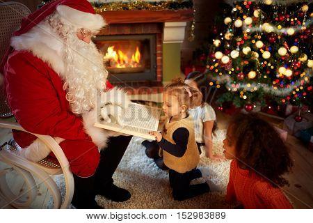 Santa Claus reads a fairy tale while three girls listen carefully