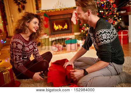 Cheerful male and female packing Christmas gifts