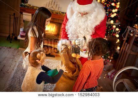 Little girls receiving Christmas presents from real Santa Claus