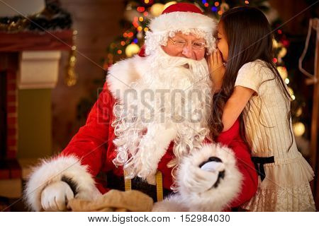 Santa Claus and Little girl,  Christmas Scene. Girl telling wish in Santa Claus's ear in front of Christmas tree