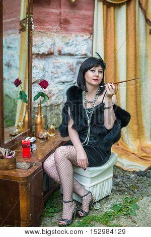 Beautiful retro woman smokes a cigarette holder