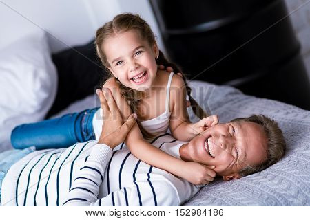Look at these cheeks. Funny little girl touching cheeks of her grandfather while having fun at home