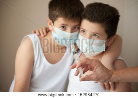 two afraid kids in a medical mask looking at hand with syringe