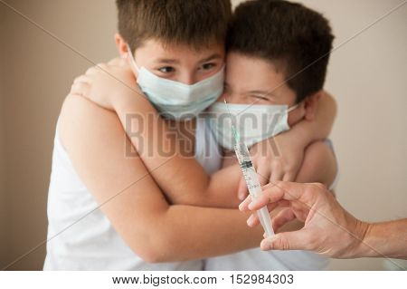 two afraid boys in a medical mask looking at hand with syringe