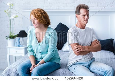 I do not understand you. Angry husband and wife sitting back to back on the bed with crossed arms