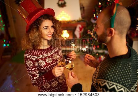 Couple congratulates New Year with sprayers and sparkling wine
