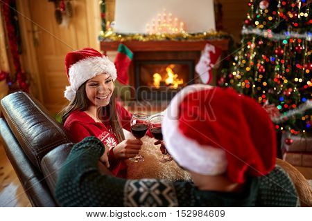 Young woman and man toasting with glass of wine in decorated home for Christmas