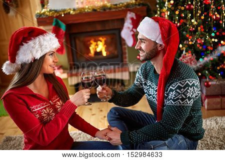 Boy and girl toasting with glasses for Christmas
