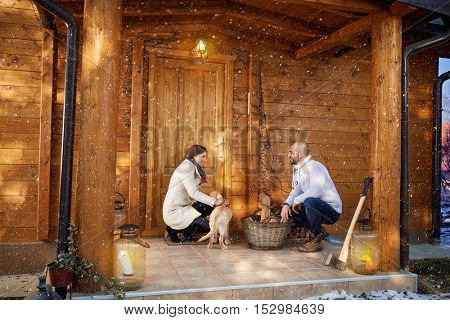 Woman and man with dog in front of weekend cottage