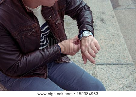 Man looks at watch waiting meeting time in a hurry