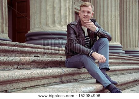 Grown adult man sitting on the steps of the Cathedral