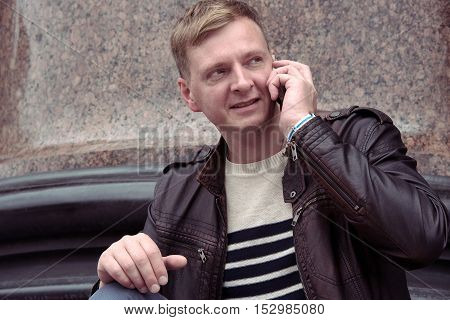 Man with phone in the city with granite columns