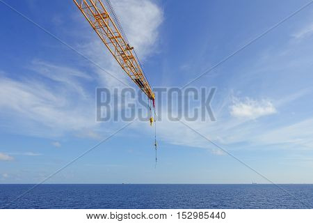 Crane boom and crane hook in the sea with sky and clouds background on offshore platform.