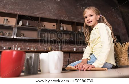 Mothers helper. Cute delighted smiling little girl holding wooden spoons and sitting on the table while having fun in the kitchen