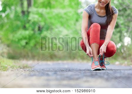 Running shoes - closeup of woman tying shoe laces. Female sport fitness runner getting ready for jogging outdoors on forest path in summer season.
