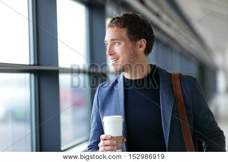 Happy businessman going to work drinking coffee - travel lifestyle or morning commute urban living. Young professional man near window in office building or at airport terminal business class flight.