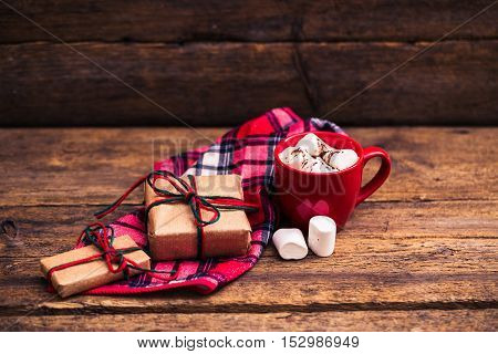 red cup with cocoa and marshmallows on wooden background. Christmas presents and candles