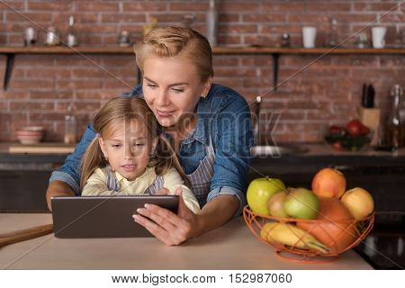 Get a nice rest. Pleasant delighted little girl looking at the tablet with her mother while sitting at the table and having fun in the kitchen