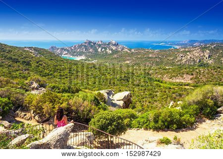 Young attractive woman enjoying stunning view from a casa diroccapina to Corsica landscape with mountains ocean Roccapina beach and pine trees Corsica France Europe.
