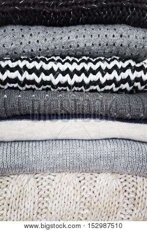 Stack Of Various Woolen Sweaters On A White Wooden Background