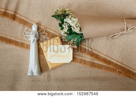 Wish Card on the Golden Present Box with White Ceramic Angel.Bouquet White Small Flowers in Brown Craft Paper with String.Rough Tablecloth Texture Background.Postcard.