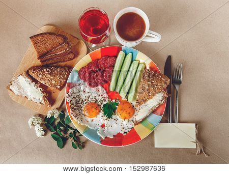 Delicious Tasty Breakfast from Eggs,Bread with Butter,Sausage on the Colorfull Plate.Coffee,Red Juice  with White Flowers.Wish Card.Knife and Folk.Brown Background.Top View
