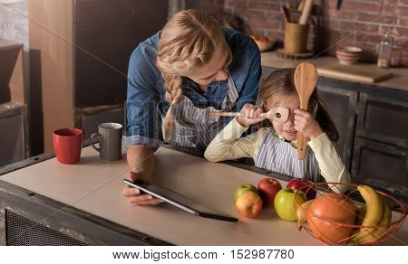 We having fun. Joyful cheerful smiling girl closing her eyes with wooden spoons while sitting at the table with her mother and expressing joy in the kitchen